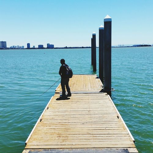 Full Length Of Man Fishing By Turquoise Sea