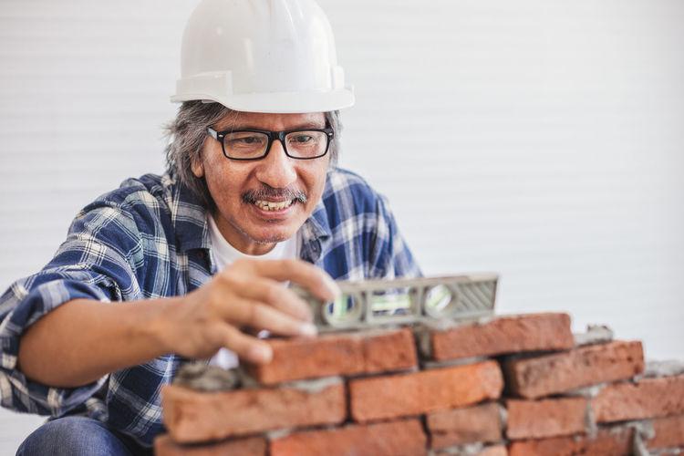 Mature man wearing hardhat making brick wall in workshop