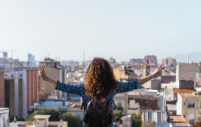 Rear view of woman with arms outstretched against cityscape