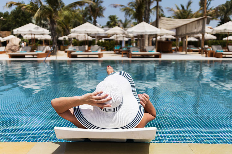 Summer vacation concept. a woman in a hat relaxing at swimming pool.