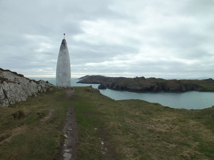 Baltimore beacon by sea against cloudy sky