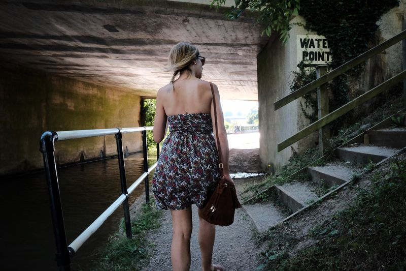 Rear view of young woman walking along canal