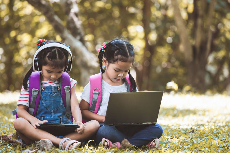 Schoolgirls Using Laptop And Digital Tablet While Sitting In Park