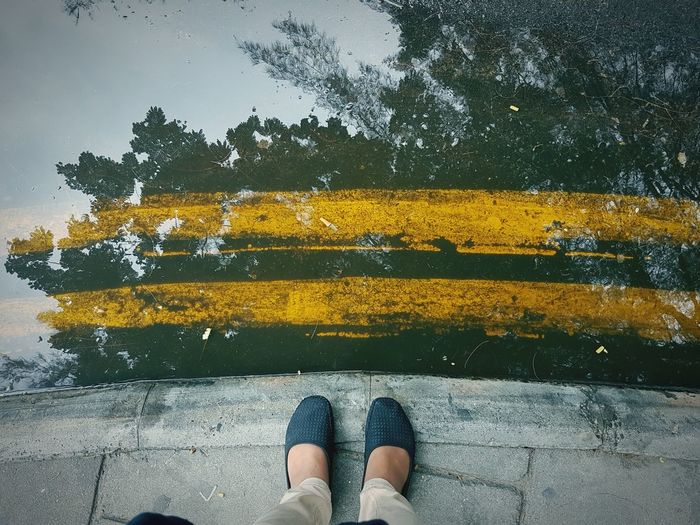 Low section of woman standing in front of puddle