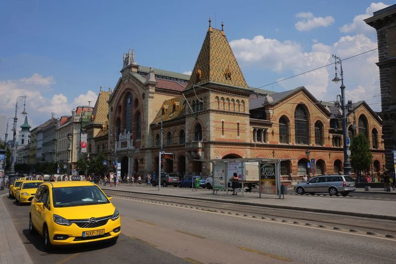 Central Market Building (built 1999), Famhaz Krt 1999 Architectural Features Architecture Blue Sky White Clouds Budapest Building Exterior Built 1999 Built Structure Capital City Central Market Composition Distant View Hungary No People Ornate Roof Outdoor Photography Road Street Sunlight And Shade Taxis Tourist Destination Trading Place Travel Destination Yellow Taxis