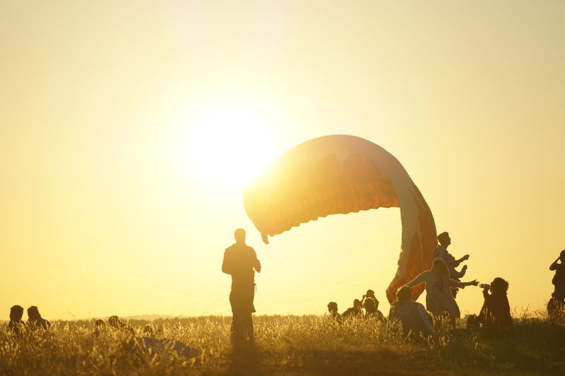 Paragliding Beauty In Nature Clear Sky Environment Field Group Of People Land Landscape Leisure Activity Lens Flare Lifestyles Men Nature Outdoors People Plant Real People Silhouette Sky Sun Sunlight Sunset