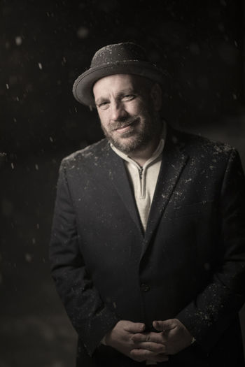 A man in his mid-40s stands for a portrait during snowfall wearing a vintage hat and jacket. Night Real People Men Nightphotography Portrait Winter Beard Snow Classic Standing Hat Man Clothing Mafia  Adult Facial Hair Front View Males  Lifestyles Looking At Camera One Person Waist Up Leisure Activity Mid Adult Men Devin Miller