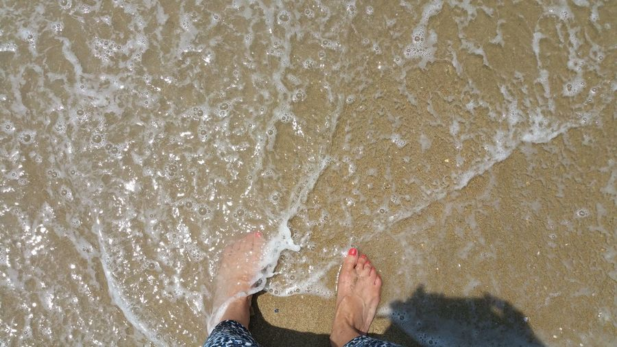 Low section of woman barefooted standing in ocean water on beach
