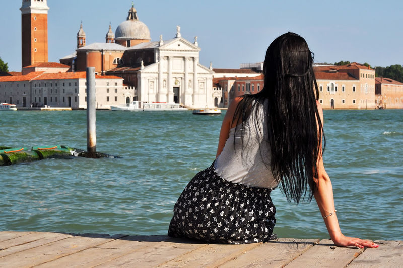 Rear view of woman looking at san giorgio maggiore while sitting on jetty