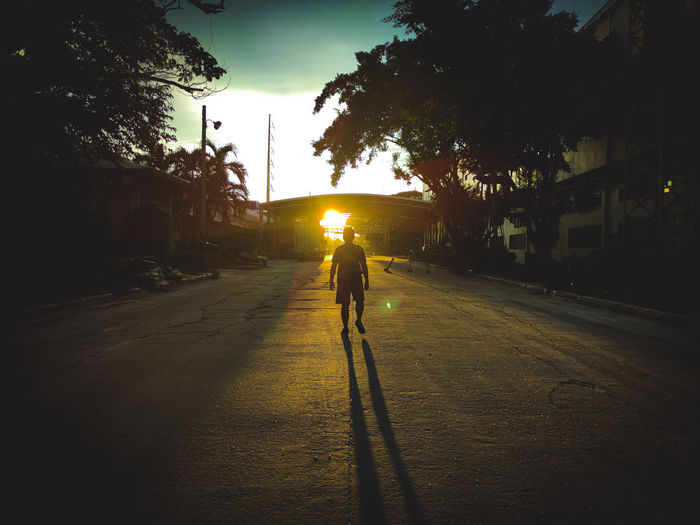 Rear view of silhouette man on street against sky at sunset