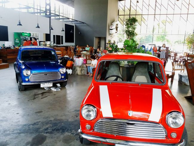 Two classic min cooper car parking at garage with people background. Red Car Mode Of Transport Land Vehicle Transportation Fire Engine Law Firefighter People City Mini Austin  Cooper British Car Small Classic Car Vintage Retro Style Old Blue Parking Garage Race