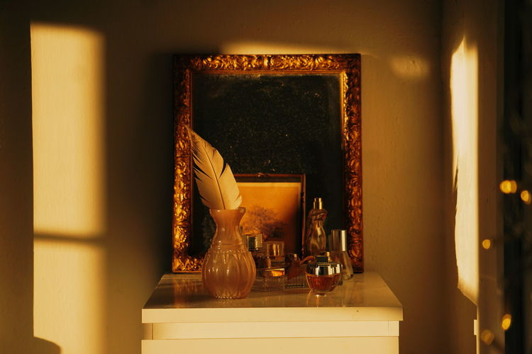 Mirror with feather and perfume sprayer on table at home