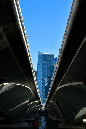 Low angle view of bridge over sea in city