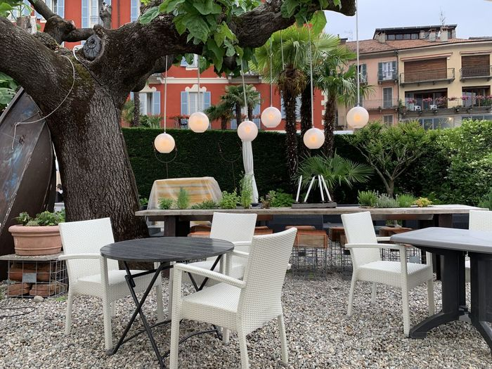 Empty chairs and tables in yard against building