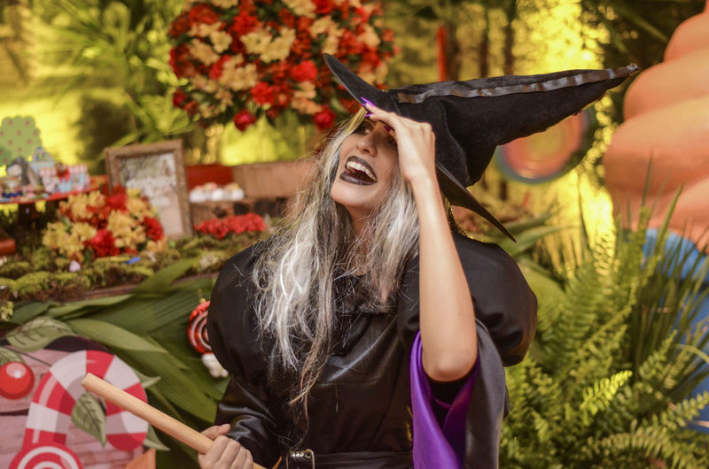 Happy woman wearing wizard costume during halloween