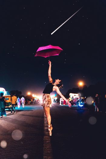 Ballet dancer holding pink umbrella while standing on street against sky at night