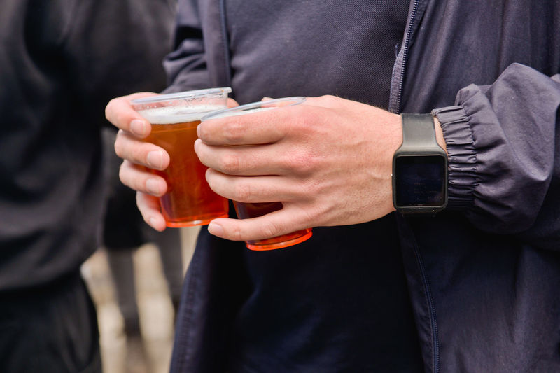 Midsection of man holding beer