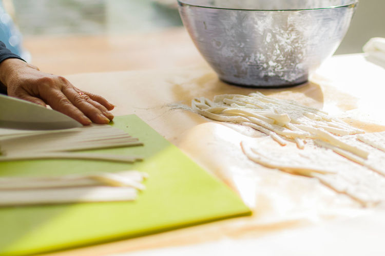 Close-up Cooking At Home Cutting Food And Drink Freshness Human Body Part Human Hand Indoors  One Person Preparation  Real People Rice Noodles Selective Focus Sunlight Table