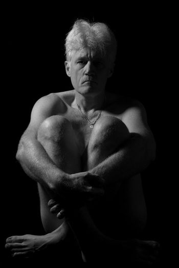 Naked mature adult man  sitting over black background