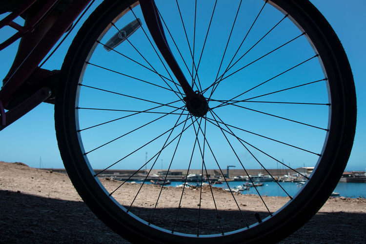 Close-up of bicycle wheel against blue sky