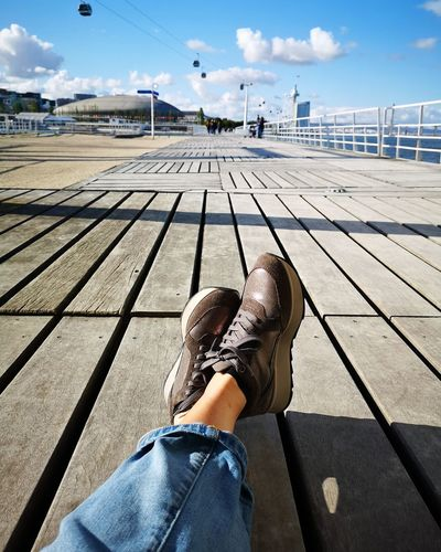 Low section of woman sitting on boardwalk during sunny day