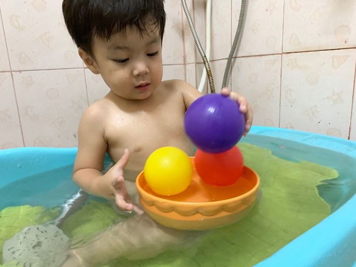 Child Childhood One Person Real People Shirtless Indoors  Baby Young Boys Bathtub Innocence Lifestyles Domestic Bathroom Playing Babyhood Domestic Room Home Toy Men Flooring