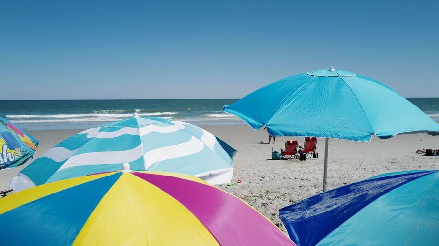 Umbrella on beach against clear blue sky