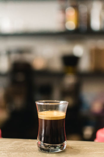 Drink Refreshment Food And Drink Glass Table Drinking Glass Focus On Foreground Household Equipment Alcohol Close-up Freshness Still Life No People Indoors  Shot Glass Wood - Material Glass - Material Bar - Drink Establishment Transparent Bar Counter Crockery
