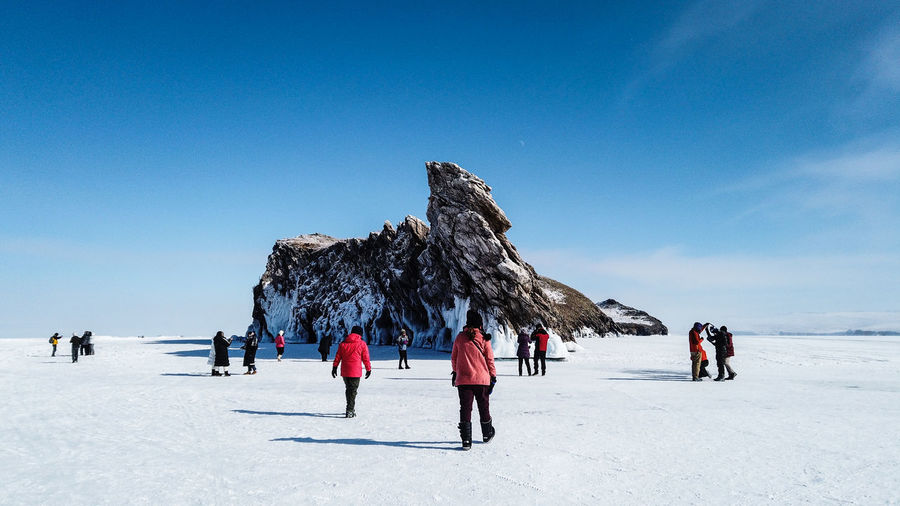 People on snow covered land against blue sky
