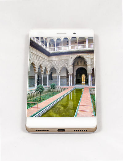 Modern smartphone with full screen picture of Seville, Spain. Concept for travel smartphone photography. All images in this composition are made by me and separately available on my portfolio Arch Architectural Column Architecture Building Building Exterior Built Structure Connection Day Glass - Material Grass Green Color History Nature No People Outdoors Plant The Past White Color Window
