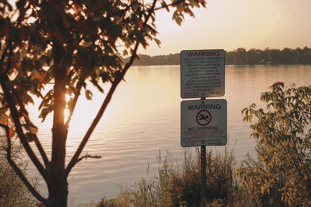 water, communication, tree, sign, plant, nature, lake, information, text, sky, sunset, information sign, no people, warning sign, beach, tranquility, beauty in nature, outdoors, guidance