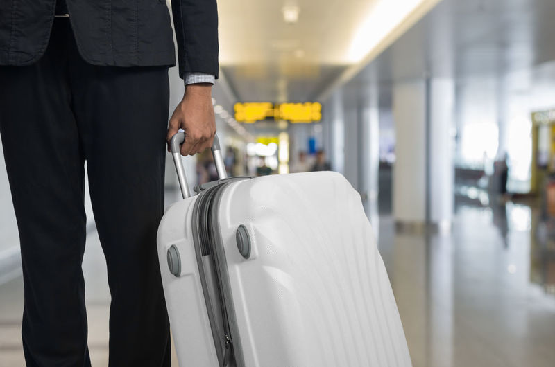 Midsection of businessman with suitcase at airport
