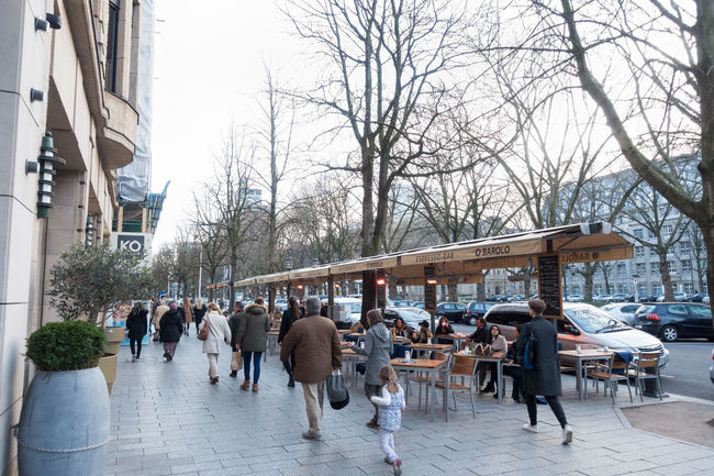 DUESSELDORF, GERMANY - MARCH 12, 2017: Unidentified shoppers stroll along the Königsallee and pass a scenic cafe with unidentified individuals Architecture Bare Tree Building Exterior Built Structure Cafe Chair City Life Citylife Day Düsseldorf Königsallee Large Group Of People Life Style Luxury Outdoors P Real People Restaurant Rhein Shopping Sidewalk Cafe Table Tree Visitors Walking