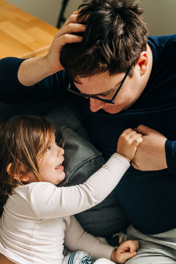 Father playing with daughter at home