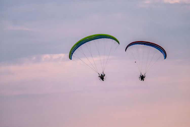Paraglider flying with paramotor during sunset Criccieth Fly Wales Wales UK Adventure Aerospace Industry Challenge Extreme Sports Flight Flying Freedom Leisure Activity Lifestyles Mid-air Outdoors Parachute Paragliding Real People Sky Sport Sunrise Sunset Uk Unrecognizable Person