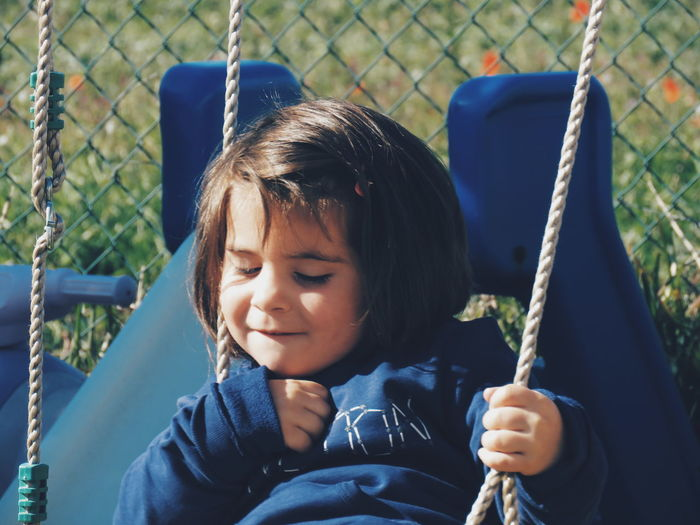 Close-up of cute girl sitting on swing at playground