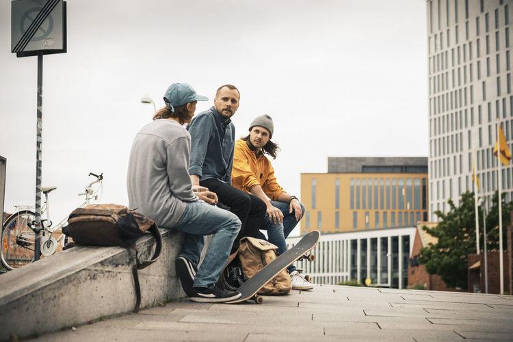 Men sitting on sidewalk in city