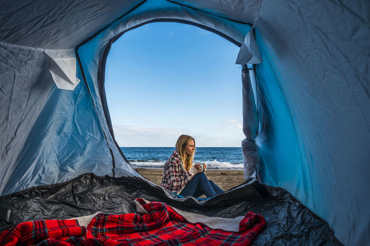 Side View Of Woman Sitting At Beach Against Blue Sky Seen Through Tent