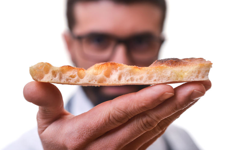 Close-up of hand holding bread against white background