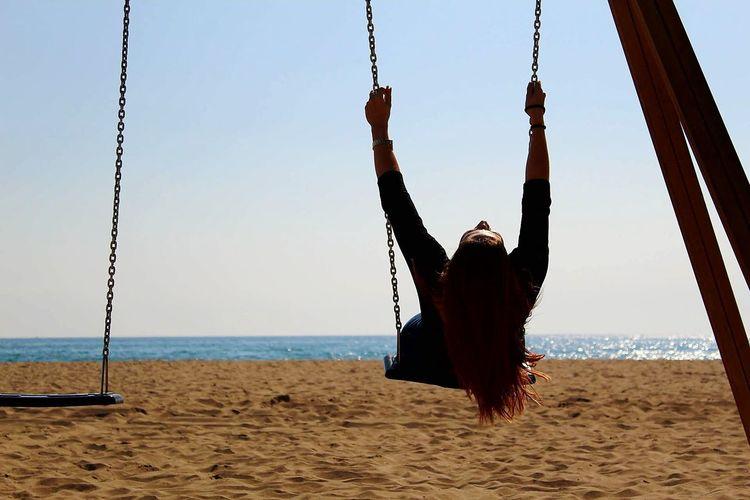 Woman swinging at beach against sky