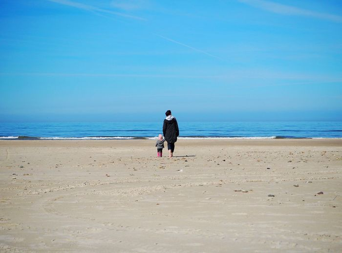 Rear View Full Length Of Mother With Daughter Walking On Sand At Beach Against Blue Sky