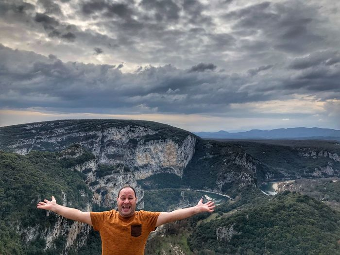 Portrait of mid adult man with arms outstretched standing on observation point against mountains