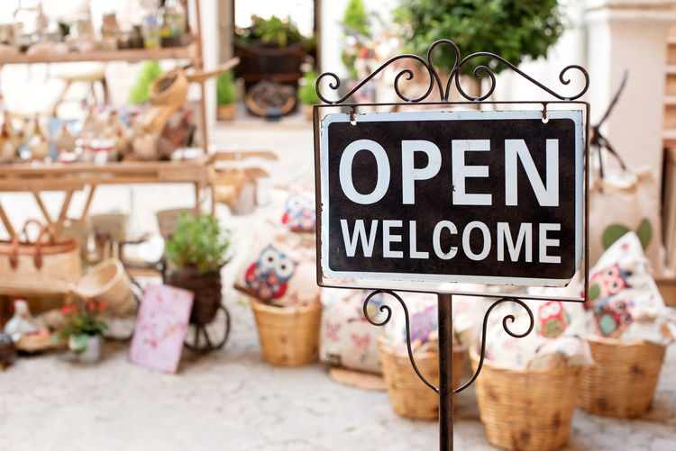 Open Welcome sign on a scrolled metal frame and pole outside a market shop selling potted plants Rural Sign Business Commerce Commercial Hospitality Information Information Sign Market Message Open Retail  Retail  Shop Sign Small Business Souvenirs Store Text Traditional Vintage Welcome