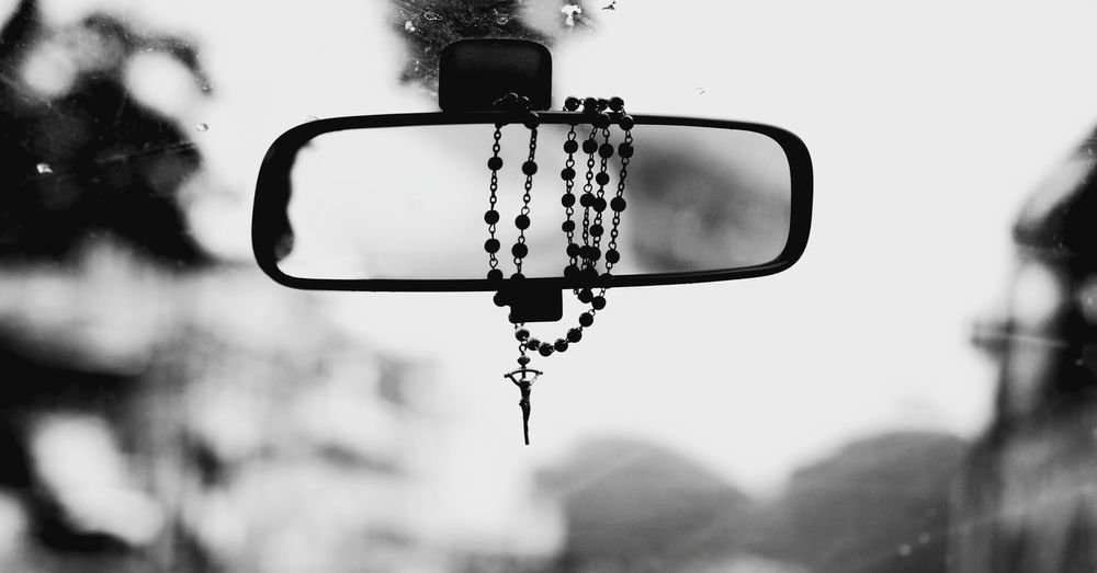 Close-Up Of Rosary Hanging On Rear-View Mirror In Car