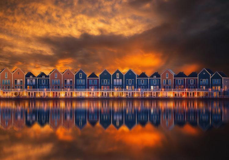 Buildings by sea against orange sky