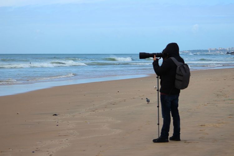 Side view of man photographing while standing at beach against sky