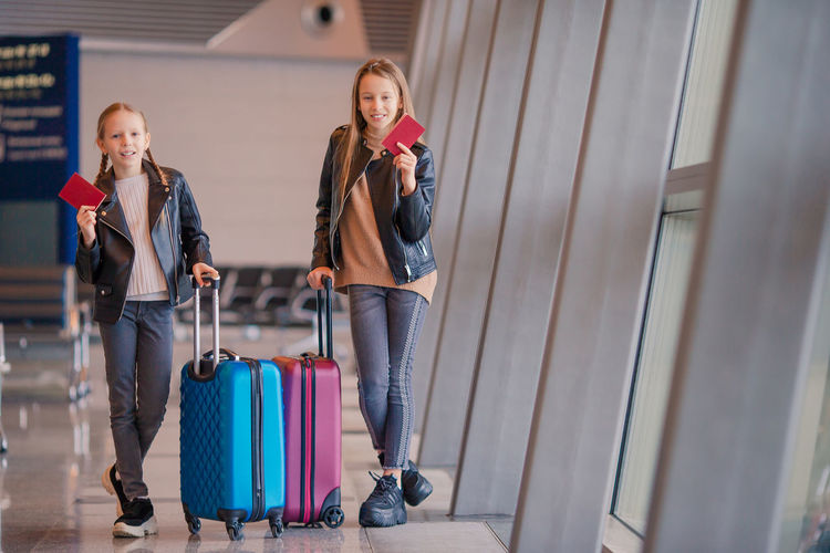Portrait of sisters holding passport while standing at airport