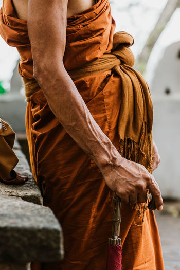 Sri Lanka Buddhism Clothing Day Focus On Foreground Hand Holding Human Body Part Human Hand Lifestyles Men Midsection Monk  Nature One Person Outdoors Real People Religion Solid Standing Three Quarter Length Traditional Clothing