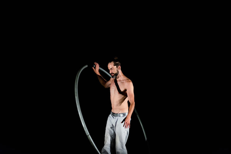 Circus Adult Arms Raised Black Background Copy Space Front View Holding Human Arm Human Limb Indoors  Men Mid Adult Muscular Build One Person Shirtless Stage Standing Strength Studio Shot Three Quarter Length Young Adult