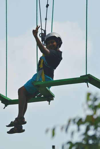 Low angle view of boy on rope course against sky